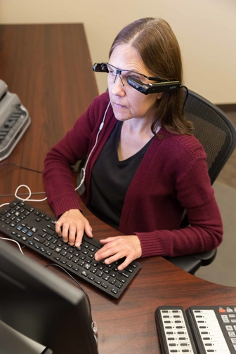 woman typing with glasses on